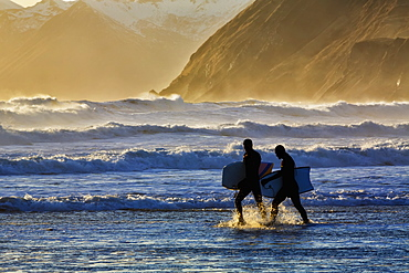 Body Surfers Walk In The Water On The Coast Of Kodiak Island During Late Afternoon, Pasagshak State Park, Kodiak Island, Alaska