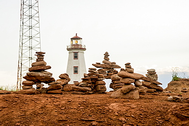 Rocks balanced in piles with a lighthouse in the background, Prince Edward Island, Canada