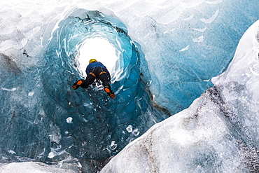 Man exploring an ice cave, South Coast, Iceland