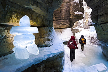 Two people exploring a canyon with ice block inukshuk in winter, Jasper National Park, Alberta, Canada