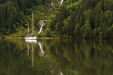 Sailboat in the Great Bear Rainforest with a waterfall along the coast, Hartley Bay, British Columbia, Canada