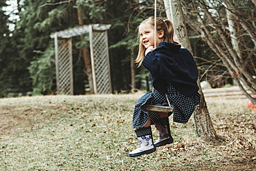 Portrait of a young girl swinging on a swing, Alberta, Canada