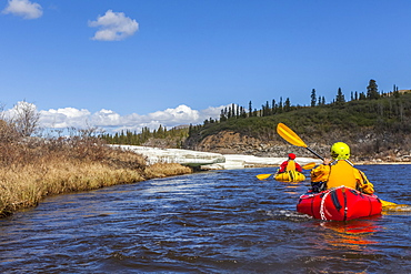 Female packrafters negotiating a tributary of the Charley River with aufeis in summer, Alaska, United States of America