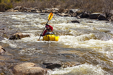 Female packrafter negotiating a technical rapid on the tributary of the Charley River with aufeis in summer, Alaska, United States of America