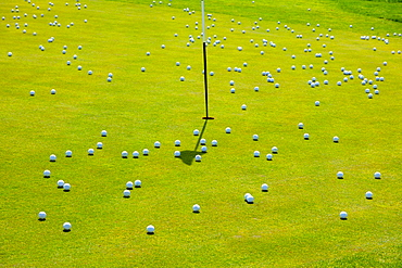 Numerous golf balls by a hole on golf course, creating chaos, Lucerne, Lucerne, Switzerland
