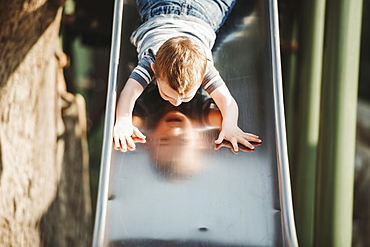 Young boy going down head-first on a playground slide, Edmonton, Alberta, Canada
