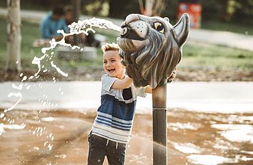 A young boy at a spray park, Edmonton, Alberta, Canada