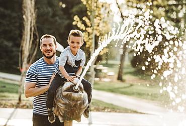 Father and young son at spray park, Edmonton, Alberta, Canada