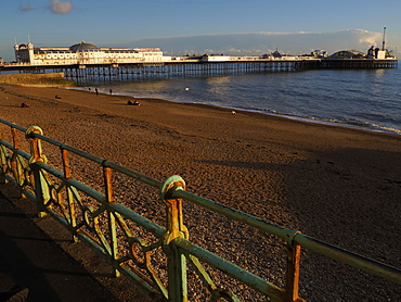 View of Brighton Pier and beach at sunset, Brighton, East Sussex, England
