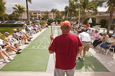 Spectators watching a shuffleboard game