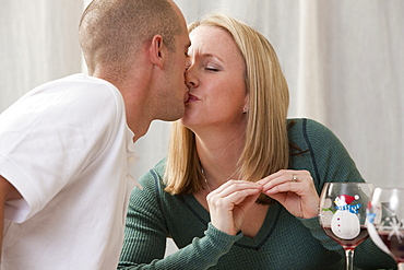 Woman signing the word 'Kiss' in American Sign Language while kissing her husband