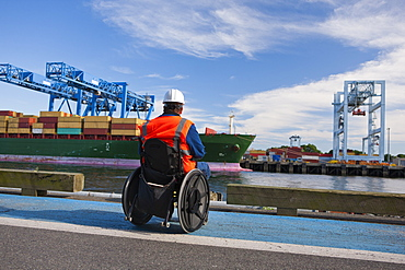 Transportation engineer in wheelchair inspecting container ship at shipping port