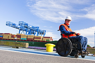 Transportation engineer in wheelchair passing bollard at shipping port