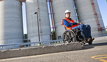 Facilities engineer in wheelchair inspecting outdoor bulk storage tanks