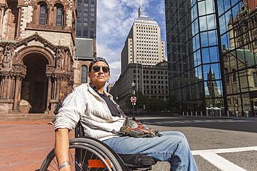 Woman with spinal cord injury crossing street, St. James Avenue, John Hancock Tower, Trinity Church, Boston, Massachusetts, USA