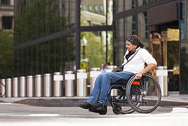 Woman with spinal cord injury crossing street, Boston, Massachusetts, USA