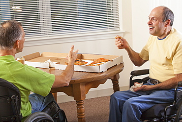 Two disabled men sitting in wheelchairs and eating pizza
