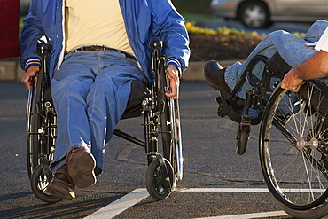 Man with Friedreich's Ataxia greeting his friend with spinal cord injury