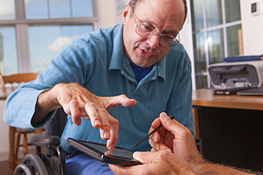 Two disabled men sitting in wheelchairs and using a digital tablet, one with deformed hands