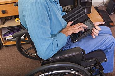Man with Friedreich's Ataxia in wheelchair using a tablet with deformed hands