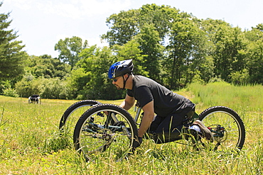 Man with spinal cord injury riding on off-road hand cycle