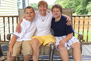 Grandmother with a prosthetic leg with her grandchildren sitting on their outdoor patio