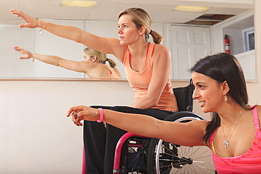Young women with spinal cord injuries stretching in a yoga studio