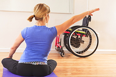Young woman with a spinal cord injury doing a yoga pose in a studio