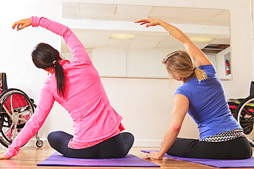 Young women with a spinal cord injuries doing a yoga poses in a studio