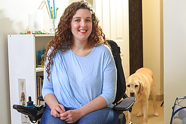 Woman with Muscular Dystrophy in her power chair with her service dog behind her