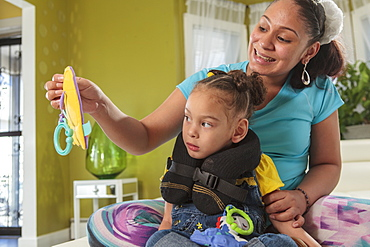 Mother showing small daughter with Cerebral Palsy a toy