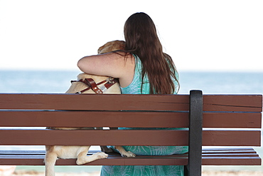 Young woman with visual impairment and her service dog hugging on a bench