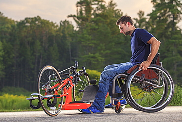 Man with spinal cord injury in his custom adaptive hand cycle getting into his wheelchair