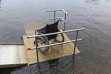 Wheelchair on a dock at a lake