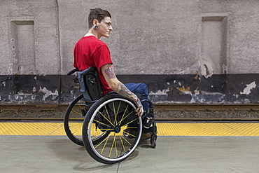 Trendy man with a spinal cord injury in wheelchair waiting for a subway train