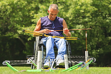 Man with spinal cord injury in wheelchair preparing for archery practice