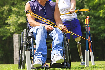 Man with spinal cord injury and woman with prosthetic leg preparing bow and arrow for practice