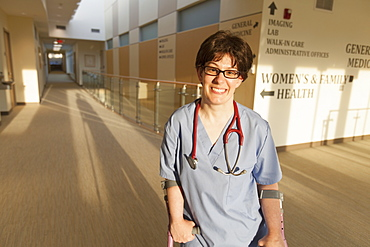 Nurse with Cerebral Palsy walking down the hallway of a clinic with her canes