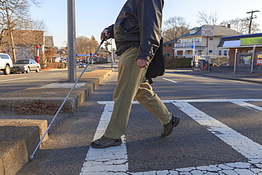 Man with congenital blindness crossing the street using his cane