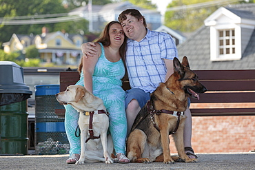 Blind couple hugging each other with their service dogs relaxing at a bench on the beach