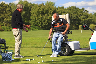Instructor helping a Man with spinal cord injury to learn golf