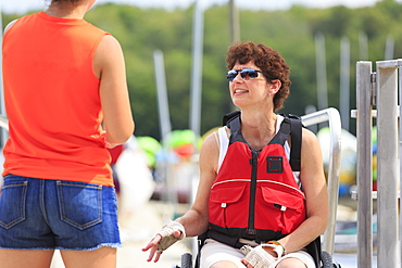 Woman with a Spinal Cord Injury talking to an instructor about using a kayak