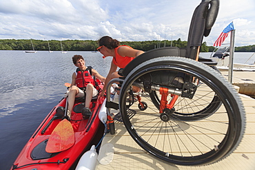Instructor helping a woman with a Spinal Cord Injury get into a kayak