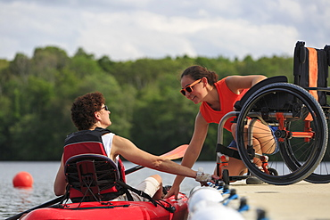 Instructor helping a woman with a Spinal Cord Injury use a kayak
