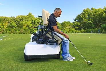 Man with spinal cord injury in an adaptive cart at golf putting green