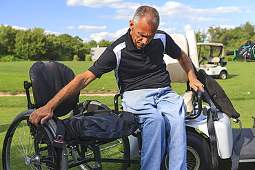 Man with spinal cord injury in an adaptive golf cart getting into his wheelchair