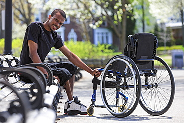 Man who had Spinal Meningitis sitting on a park bench near his wheelchair