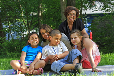 Happy Hispanic family with Autistic boy sitting together in a park