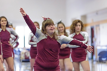 Cheerleader with Down Syndrome cheering with her friends
