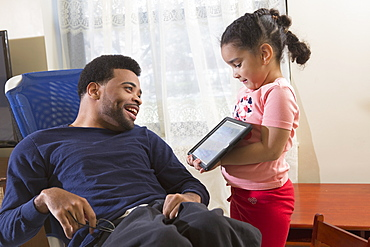 Happy African American man with Cerebral Palsy with his daughter using a tablet at home